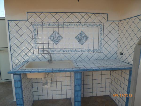 Cucina in muratura, con piastrelle color azzurro-bianco lucido