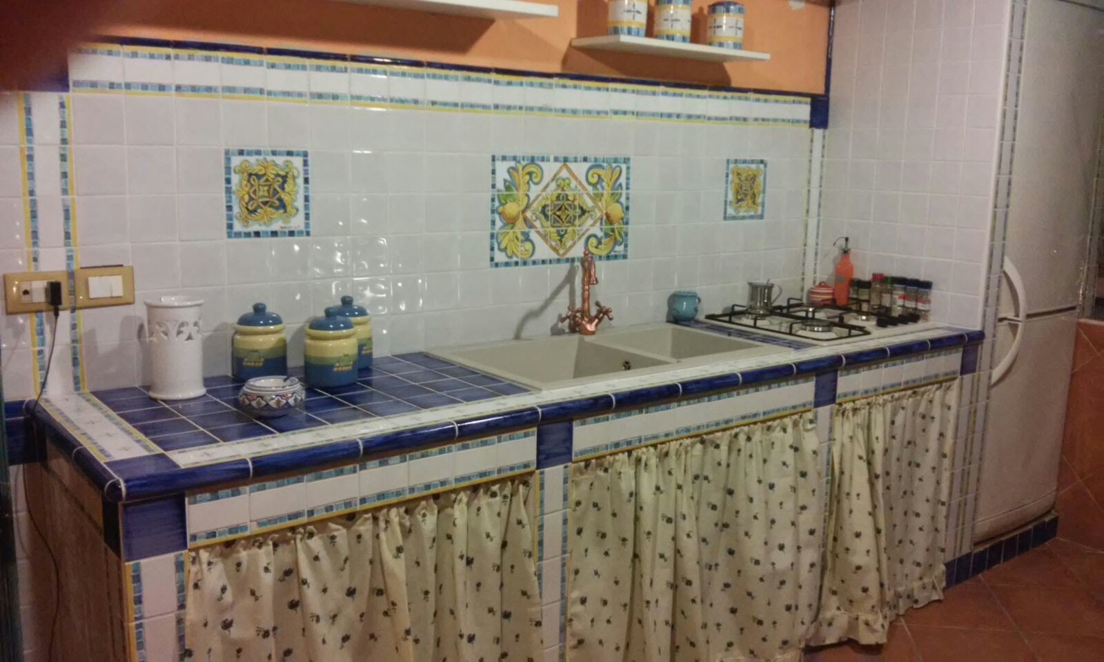 Cucina in muratura, con quadri su piastrelle, vista frontale